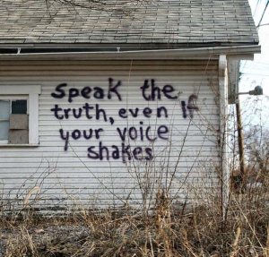 "A shabby whiteboard house, with the following words graffitied in black paint: ""Speak the truth, even if your voice shakes."""