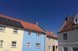 Attractive coloured houses against a blue sky, representing time away from home