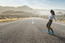 Woman riding skateboard on highway metaphor of future journey