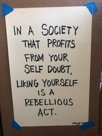 A poster by Caroline Caldwell, which reads, in a society that profits from your self doubt, liking yourself is a rebellious act.